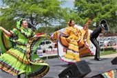 Women dancing in colorful dresses during previous Cinco de Mayo Celebration