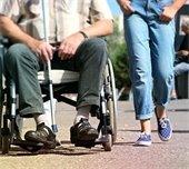 girl walking next to man in wheelchair