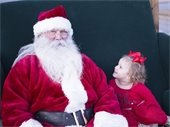 Young girl wearing red dress seated next to Santa