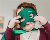 Young boy wearing green superhero mask and matching green cape