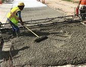 Employees pouring concrete during road repair