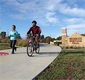 man rides bike and woman runs on trail