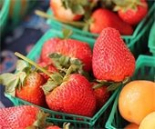 Baskets of strawberries and oranges at the marketplace
