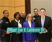 "Family and police colleagues of retired Officer Jon V. Latimore. Holding a replica of street sign that says ""Officer Jon V. Latimore Dr."""