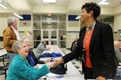 Neighborhood Services Manager shaking hands with smiling resident during a neighborhood leadership meeting