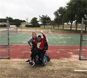 Fifth grader, Jamonta, pictured with his teacher Fredina Guevara posing at tennis court gate entry