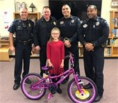 Four Mesquite police officers pictured with a young girl and a pink bike she donated to the Santa Cop toy drive