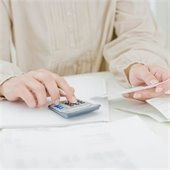 Woman's hands with calculator in one and piece of paper in the other. She appears to be paying bills.