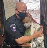 Officer Gafford and resident hug after she gives him citizen commendation
