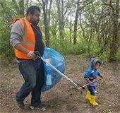dad and son pick up trash during trash bash