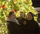 Two women and young boy smiling in front of lit Christmas tree in Downtown Mesquite