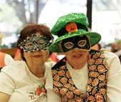 Two female senior residents posting together wearing masquerade masks
