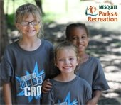 "Three young kids wearing ""Mesquite Blast Camp"" shirts smiling at the camera."