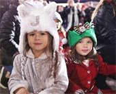 Two young girls smiling at camera during a holiday event in Mesquite