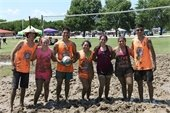 Group of friends covered in mud standing side by side, one friend holding a volleyball