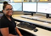 Female dispatcher sitting at her station smiling at the camera