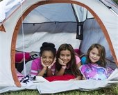 Three young girls pictured hanging out in camping tent