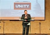 """Mayor Pickett leading prayer at podium with """"Pray for America"""" slide on projector behind him"""