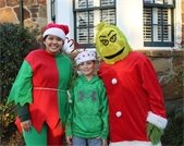 Young boy pictured with event volunteer wearing an elf costume and event volunteer wearing Grinch costume