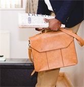 man holding newspaper and briefcase