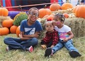 Three young kids posting together on a pumpkin patch at PumpkinFest event