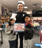 Officer Contreras posing holding books with two students