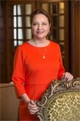 Cecilia Abbott wearing red dress posed standing behind a chair smiling at camera
