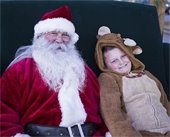 Young boy dressed as a reindeer posing with Santa
