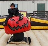 Boy riding pumpkin at pumpkinfest event