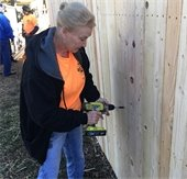 volunteer works on new fence during addressing mesquite day