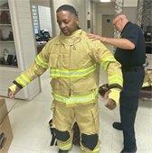 firefighter getting dressed in bunker gear