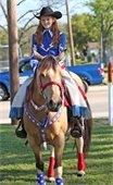 Girl riding horse during previous Mesquite Rodeo Parade