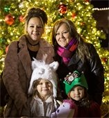 Two women and their two daughters smiling in front of lit Christmas tree in Downtown Mesquite