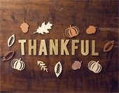 Wood table background with the word THANKFUL in gold cutout letters; decorative autumn-themed cutouts of leaves surrounding the letters