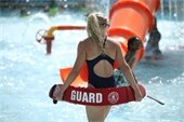 Female lifeguard in black swimsuit holding red lifeguard float around her as she watches children play in pool