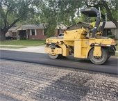 Yellow construction vehicle milling a residential road in Mesquite.