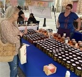 woman  talks to farmers market vendor