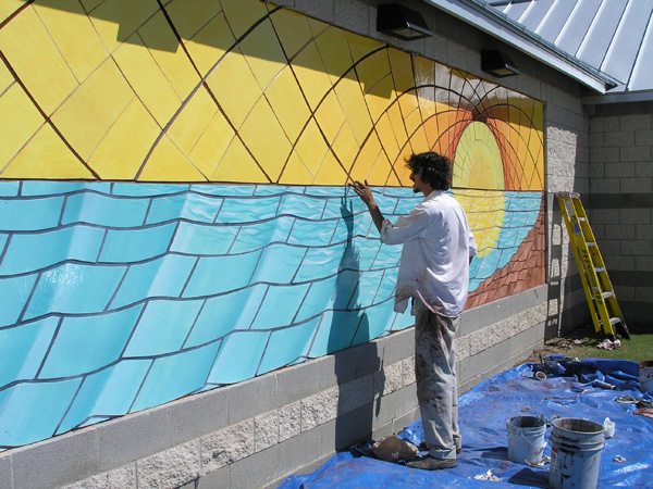 Dakota Warren, the artist, at work on the mural.