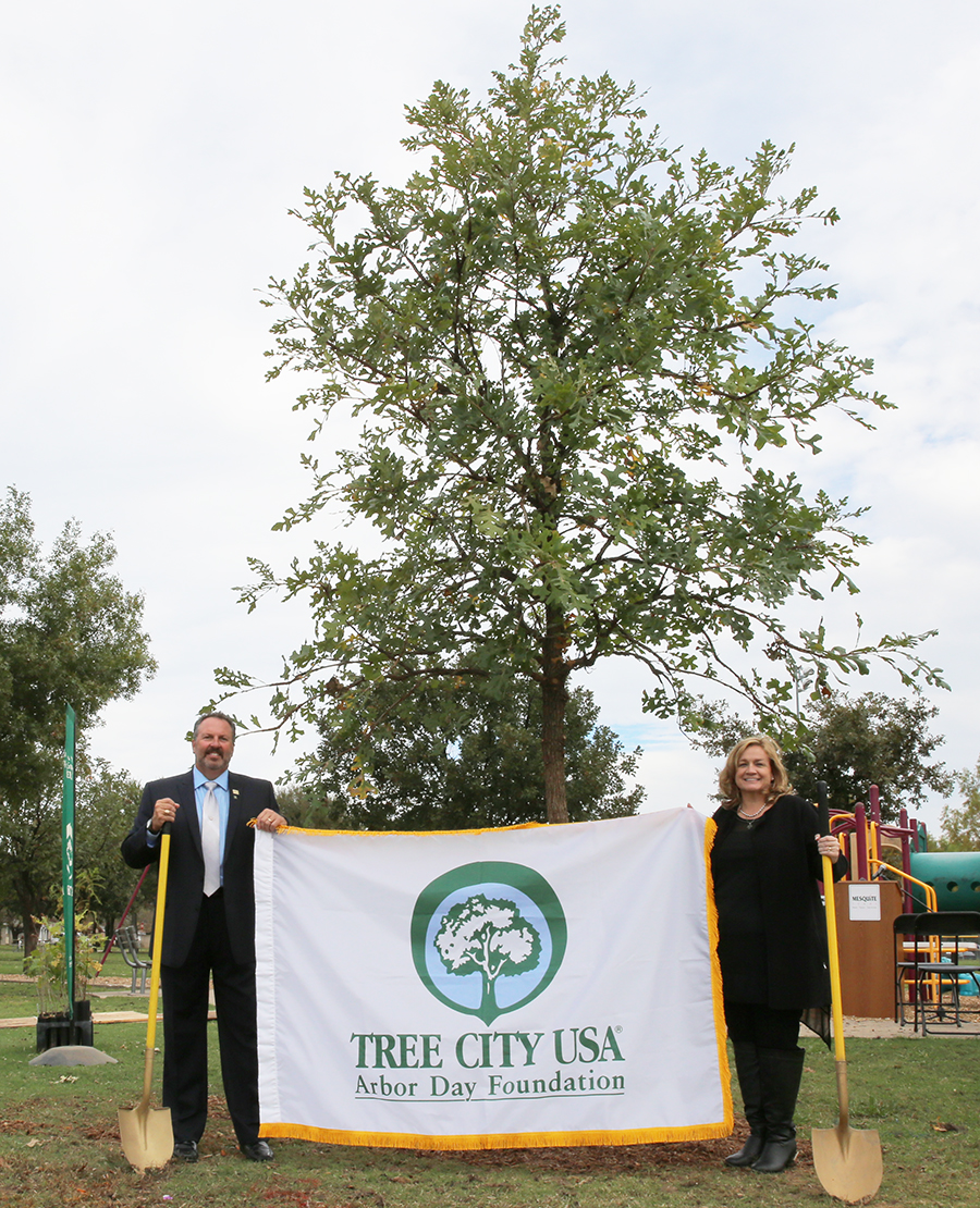 11-6-15 Arbor Day-Municipal Arborist Travis Sales and KMB Exec Dir Paige Swiney celebrate 25 yrs of Mesquite as a Tree City USA at new tree planted at Hamby Elem.jpg
